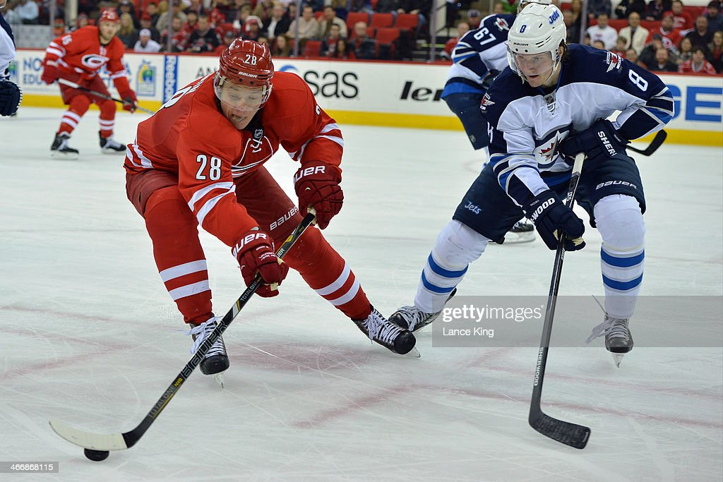 <a gi-track='captionPersonalityLinkClicked' href=/galleries/search?phrase=Alexander+Semin&family=editorial&specificpeople=206654 ng-click='$event.stopPropagation()'>Alexander Semin</a> #28 of the Carolina Hurricanes controls the puck against <a gi-track='captionPersonalityLinkClicked' href=/galleries/search?phrase=Jacob+Trouba&family=editorial&specificpeople=8050718 ng-click='$event.stopPropagation()'>Jacob Trouba</a> #8 of the Winnipeg Jets at PNC Arena on February 4, 2013 in Raleigh, North Carolina. The Jets defeated the Hurricanes 2-1.