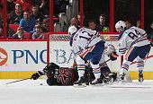 Alexander Semin of the Carolina Hurricanes goes down in front of the net of Richard Bachman of the Edmonton Oilers as Rob Klinkhammer and Oscar...