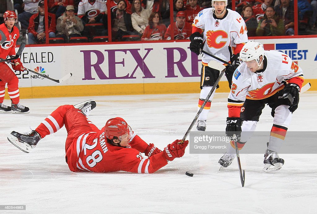 <a gi-track='captionPersonalityLinkClicked' href=/galleries/search?phrase=Alexander+Semin&family=editorial&specificpeople=206654 ng-click='$event.stopPropagation()'>Alexander Semin</a> #28 of the Carolina Hurricanes goes down on the ice while battling against Paul Byron #32 of the Calgary Flames during their NHL game at PNC Arena on January 13, 2014 in Raleigh, North Carolina.