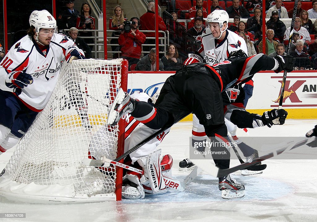 Alexander Semin #28 of the Carolina Hurricanes is tripped up in the crease ahead of Michal Neuvirth #30 of the Washington Capitals early in the first period of their NHL game at PNC Arena on March 14, 2013 in Raleigh, North Carolina.