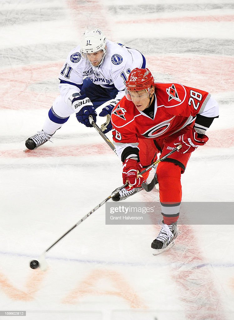 Alexander Semin #28 of the Carolina Hurricanes moves the puck against Tom Pyatt #11 of the Tampa Bay Lightning during play at PNC Arena on January 22, 2013 in Raleigh, North Carolina. Tampa Bay won 4-1.