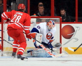 Alexander Semin of the Carolina Hurricanes posts at the top of the crease waiting for a rebound as Anders Nilsson of the New York Islanders swallows...