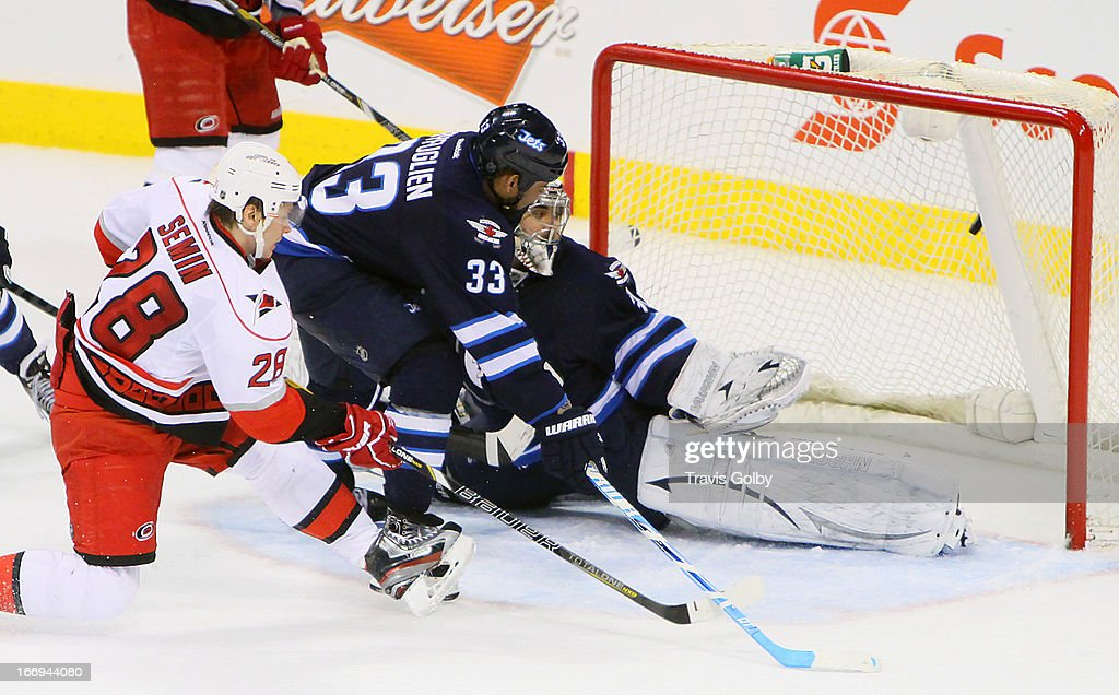 Alexander Semin #28 of the Carolina Hurricanes shoots the puck past goaltender Ondrej Pavelec #31 and defenseman Dustin Byfuglien #33 of the Winnipeg Jets for a third-period goal at the MTS Centre on April 18, 2013 in Winnipeg, Manitoba, Canada.