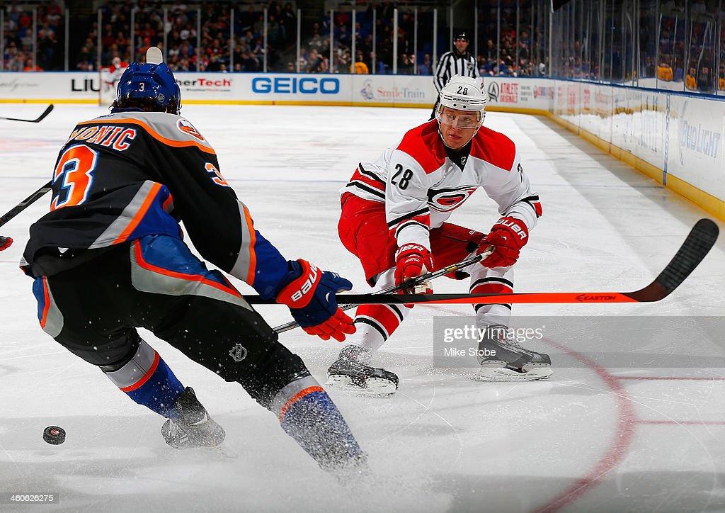 Alexander Semin #28 of the Carolina Hurricanes skates against Travis Hamonic #3 of the New York Islanders at Nassau Veterans Memorial Coliseum on January 4, 2014 in Uniondale, New York. The Hurricanes defeated the Islanders 3-2.