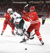 Alexander Semin of the Carolina Hurricanes stick checks a puck away from Marco Scandella of the Minnesota Wild during their NHL game at PNC Arena on...