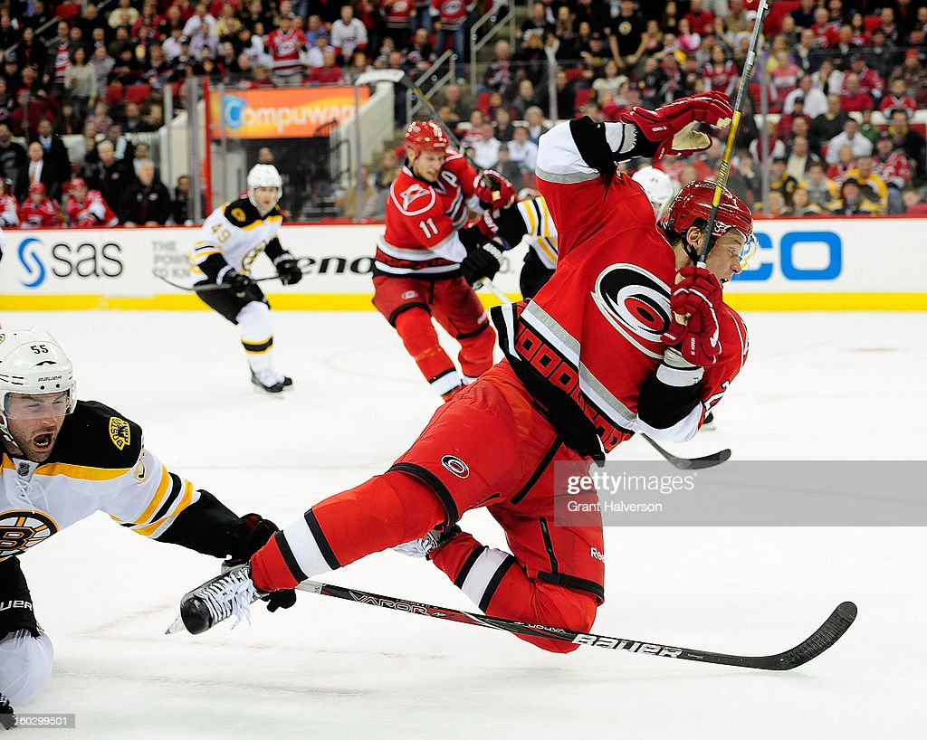 Alexander Semin #28 of the Carolina Hurricanes trips over the stick of Johnny Boychuk #53 of the Boston Bruins during play at PNC Arena on January 28, 2013 in Raleigh, North Carolina.