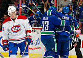 Alexander Semin of the Montreal Canadiens skates away as Alexander Edler and Christopher Tanev of the Vancouver Canucks celebrate a goal during their...
