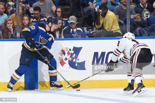 Alexander Steen of the St Louis Blues and Alex DeBrincat of the Chicago Blackhawks look for control of the puck at Scottrade Center on October 18...