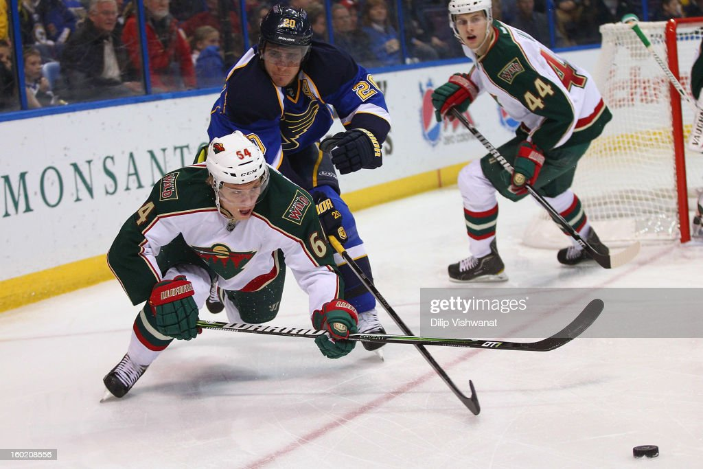 Alexander Steen #20 of the St. Louis Blues and Mikael Granlund #64 of the Minnesota Wild battle for control of a loose puck at the Scottrade Center on January 27, 2013 in St. Louis, Missouri.