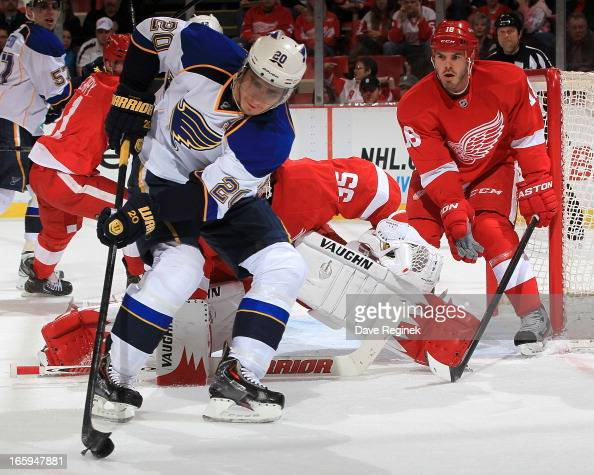 Alexander Steen of the St Louis Blues handles the puck as goalie Jimmy Howard and Ian White of the Detroit Red Wings both protect the net during a...