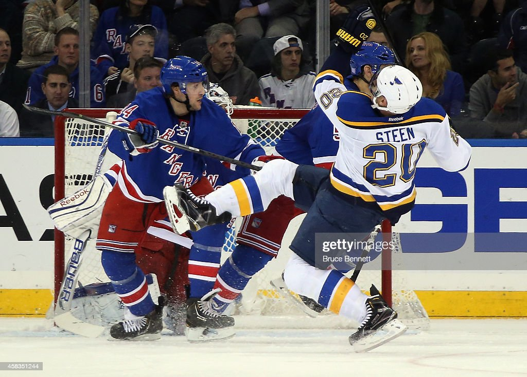 Alexander Steen of the St Louis Blues is upended by Chris Mueller of the New York Rangers during the second period at Madison Square Garden on...