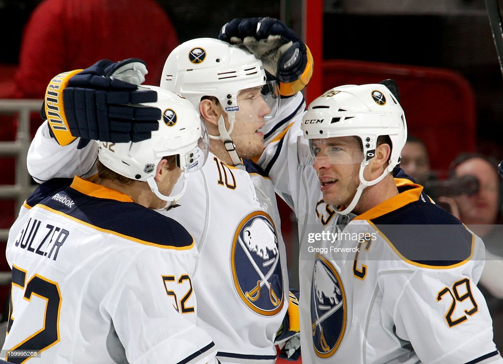 Alexander Sulzer #52 and Christian Ehrhoff #10 of the Buffalo Sabres celebrate a second-period goal scored by <a gi-track='captionPersonalityLinkClicked' href=/galleries/search?phrase=Jason+Pominville&family=editorial&specificpeople=570525 ng-click='$event.stopPropagation()'>Jason Pominville</a> #29 against the Carolina Hurricanes of the Buffalo Sabres during their NHL game at PNC Arena on January 24, 2013.