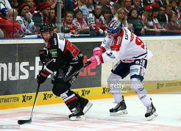 Alexander Sulzer of Koelner Haie and Marcel Noebels of Eisbaeren Berlin battle for the puck during the DEL Ice Hockey match between Koelner Haie and...