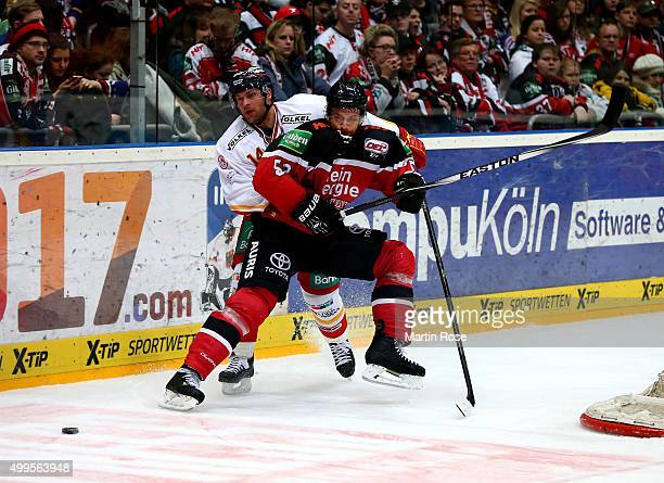 Alexander Sulzer of Koelner Haie and Norm Milley of Duesseldorfer EG battle for the puck during the DEL Ice Hockey match between Koelner Haie and...