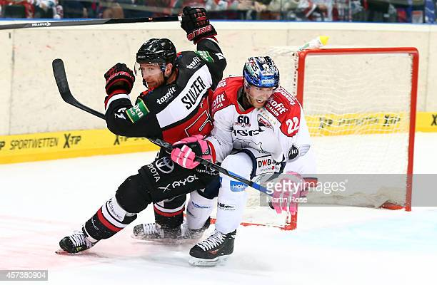 Alexander Sulzer of Koelner Haie skates against Barry Tallackson of Eisbaeren Berlin during the DEL Ice Hockey match between Koelner Haie and...