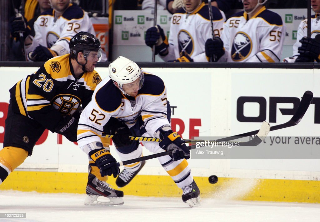 Alexander Sulzer #52 of the Buffalo Sabres and Daniel Paille #20 of the Boston Bruins battle for the puck during a game at the TD Garden on January 31, 2013 in Boston, Massachusetts.