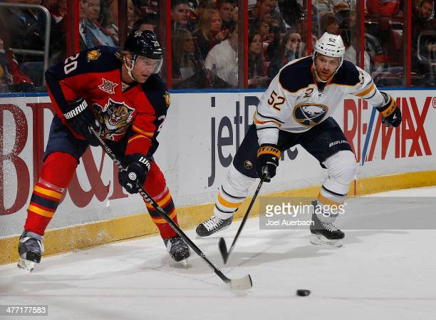 Alexander Sulzer of the Buffalo Sabres and Sean Bergenheim of the Florida Panthers skate after a loose puck during firstperiod action at the BBT...