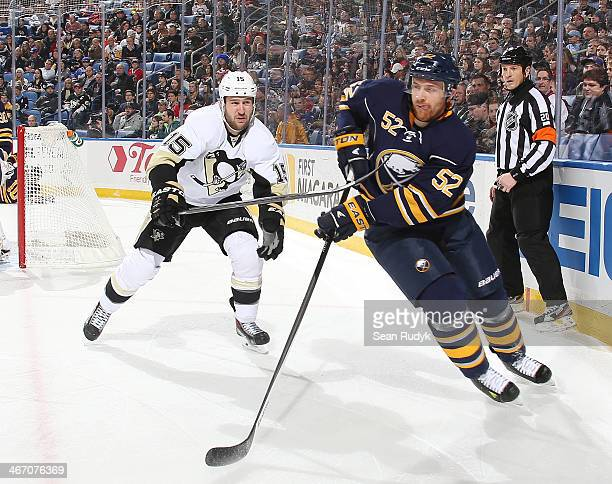 Alexander Sulzer of the Buffalo Sabres passes the puck away as Tanner Glass of the Pittsburgh Penguins reaches in from behind at First Niagara Center...