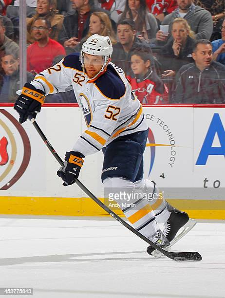 Alexander Sulzer of the Buffalo Sabres plays the puck against the New Jersey Devils during the game at the Prudential Center on November 30 2013 in...