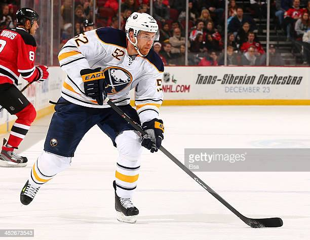 Alexander Sulzer of the Buffalo Sabres takes the puck in the third period against the New Jersey Devils at Prudential Center on November 30 2013 in...