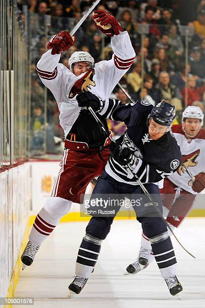 Alexander Sulzer of the Nashville Predators checks Scottie Upshall of the Phoenix Coyotes during an NHL game on February 19 2011 at Bridgestone Arena...