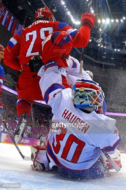 Alexander Syomin of Russia trips over Lars Haugen of Norway at the net during the Men's Ice Hockey Qualification Playoff game on day eleven of the...