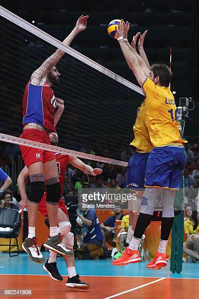 Alexander Volkov of Russia spikes at the Brazil defence during the Men's Volleyball Semifinal match on Day 14 of the Rio 2016 Olympic Games at the...