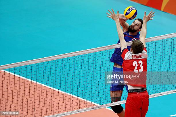 Alexander Volkov of Russia spikes past Mateusz Bieniek of Poland during a Men's Preliminary Pool B match on Day 8 of the Rio 2016 Olympic Games at...