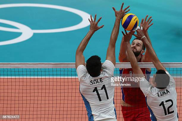 Alexander Volkov of Russia spikes the ball against Facundo Conte and Sebastian Sole of Argentina during the men's qualifying volleyball match between...
