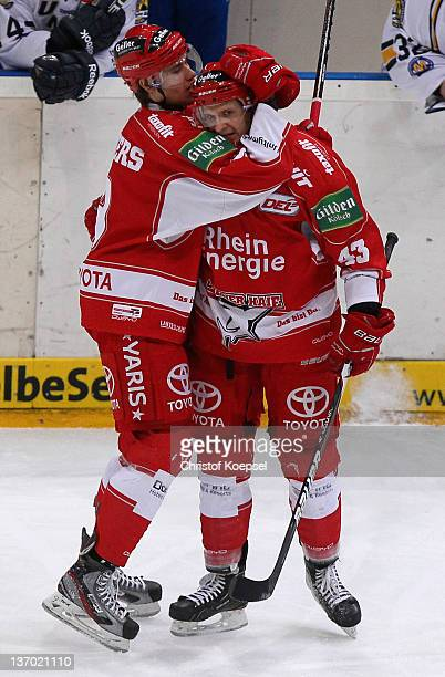 Alexander Weiss of Koelner Haie celebrates the thirKasper Sarup Sonderggaardoal with Philip Riefers during the DEL match between Koelner Haie and EHC...