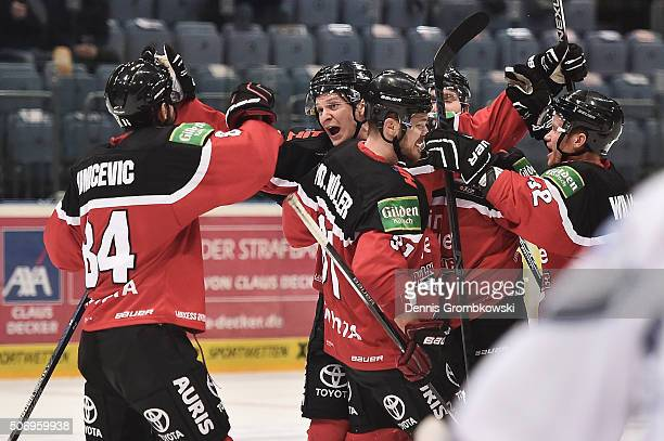 Alexander Weiss of Koelner Haie celebrates with team mates as he scores the first goal during the DEL Ice Hockey match between Koelner Haie and...