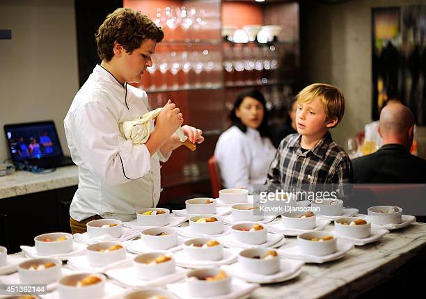 Alexander Weiss the MasterChef Junior Winner instructs invited guest Luke Fraunces how to fill a cannoli as they prepare desert in Drago Centro...