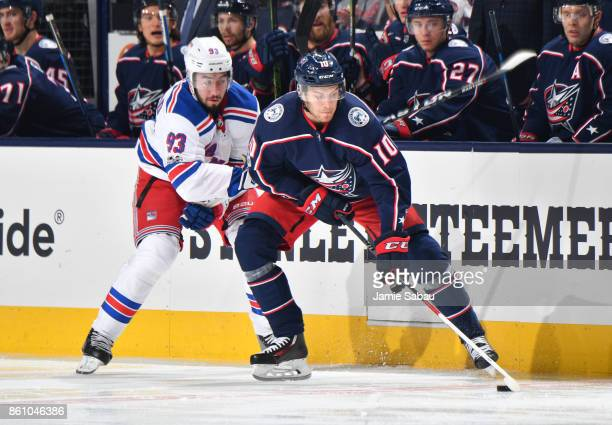 Alexander Wennberg of the Columbus Blue Jackets attempts to keep the puck from Mika Zibanejad of the New York Rangers during the second period of a...