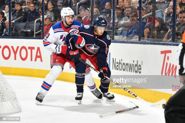 Alexander Wennberg of the Columbus Blue Jackets attempts to keep the puck from Mika Zibanejad of the New York Rangers during the third period of a...