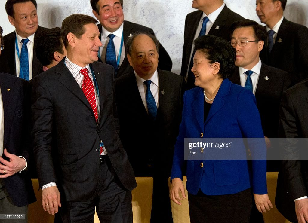 Alexander Zhukov, head of the 2022 Evaluation Commission for the International Olympic Committee (IOC), at left, and Chinese Vice Premier Liu Yandong, second from right, talk after posing for a group photo with members of the IOC's 2022 Evaluation Commission and Beijing's 2022 Winter Olympics bid committee on March 24, 2015 in Beijing, China.