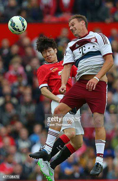 Alexander Zickler of Bayern Munich All Stars wins the ball ahead of Jisung Park of Manchester United Legends during the Manchester United Foundation...