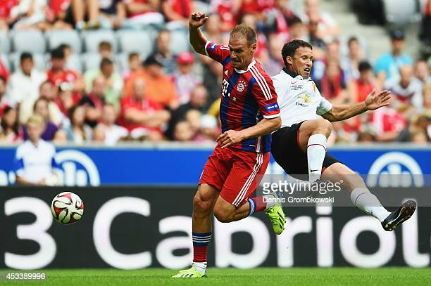 Alexander Zickler of FCB AllStars is challenged by Ronny Johnsen of ManUtd Legends during the friendly match between FC Bayern Muenchen AllStars and...