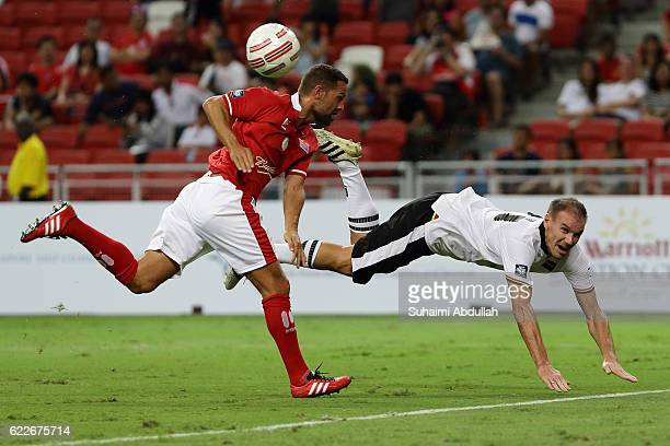 Alexander Zickler of Germany heads the ball under pressure from Luke Young of England during the Battle of Europe match between England Masters and...