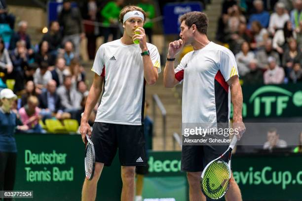 Alexander Zverev of Germany and Mischa Zverev of Germany talk to each other while playing against Ruben Bemelmans of Belgium and Joris De Loore of...
