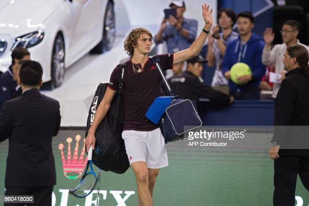 Alexander Zverev of Germany holding his broken racquet waves to the crowd after losing his men's third round singles match against Juan Martin Del...