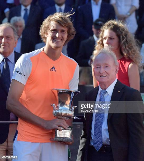 Alexander Zverev of Germany receives the trophy from the hands of former Australian player Rod Laver after winning the ATP Tennis Open final against...