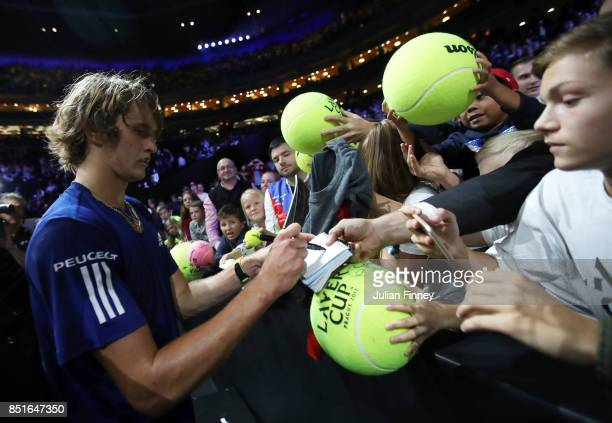 Alexander Zverev of Team Europe signs tennis balls after winning his singles match against Denis Shapovalov of Team World on the first day of the...