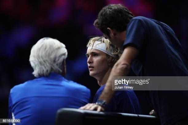 Alexander Zverev of Team Europe speaks to Bjorn Borg Captain of Team Europe and Roger Federer of Team Europe during his singles match against Denis...