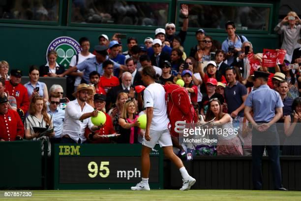 Alexandr Dolgopolov of Ukraine walks off after having to retire through injury after his Gentlemen's Singles first round match against Roger Federer...