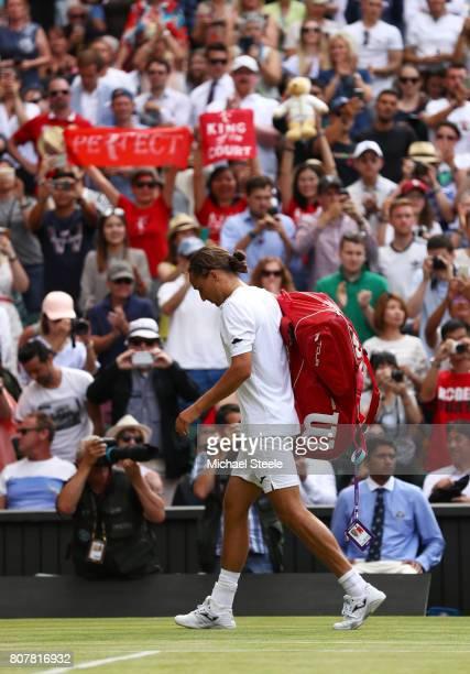 Alexandr Dolgopolov of Ukraine walks off court as he retires injured after the Gentlemen's Singles first round match against Roger Federer of...