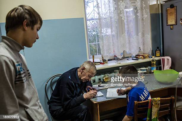 Alexandr Fedorovich the livein supervisor at a facility for atrisk teenage boys run by City Without Drugs helps one of the boys with his homework on...