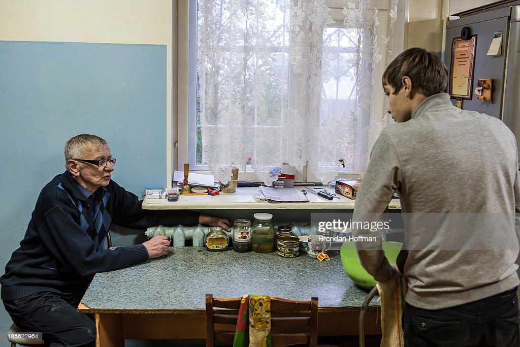 Alexandr Fedorovich (L), the live-in supervisor at a facility for at-risk teenage boys run by City Without Drugs, advises a boy tasked with cooking dinner on October 16, 2013 in Yekaterinburg, Russia. Nine boys, many of whom were either experimenting with drugs or had dropped out of school, live at the group home, where school attendance and homework are mandatory. City Without Drugs is a well-known narcotics treatment program in Russia founded by Yevgeny Roizman, who was elected mayor of Yekaterinburg in September 2013.