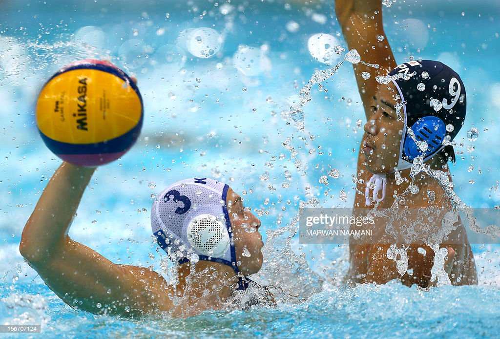 Alexandr Godovanyuk (L) of Kazakhstan attempts to scores against Japan under the pressure of Koji Takei during the two teams game in at the 9th Asian Swimming Championships in Dubai, on November 19, 2012. AFP PHOTO/MARWAN NAAMANI