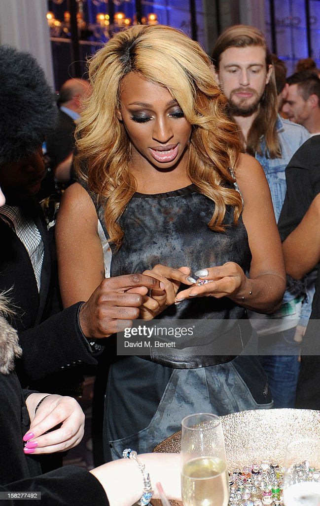 Alexandra Burke admires the jewellery as she attends a champagne reception celebrating the launch of Chamilia and Ernest Jones' partnership with Make-A-Wish International at the Corinthia Hotel on December 12, 2012 in London, England.