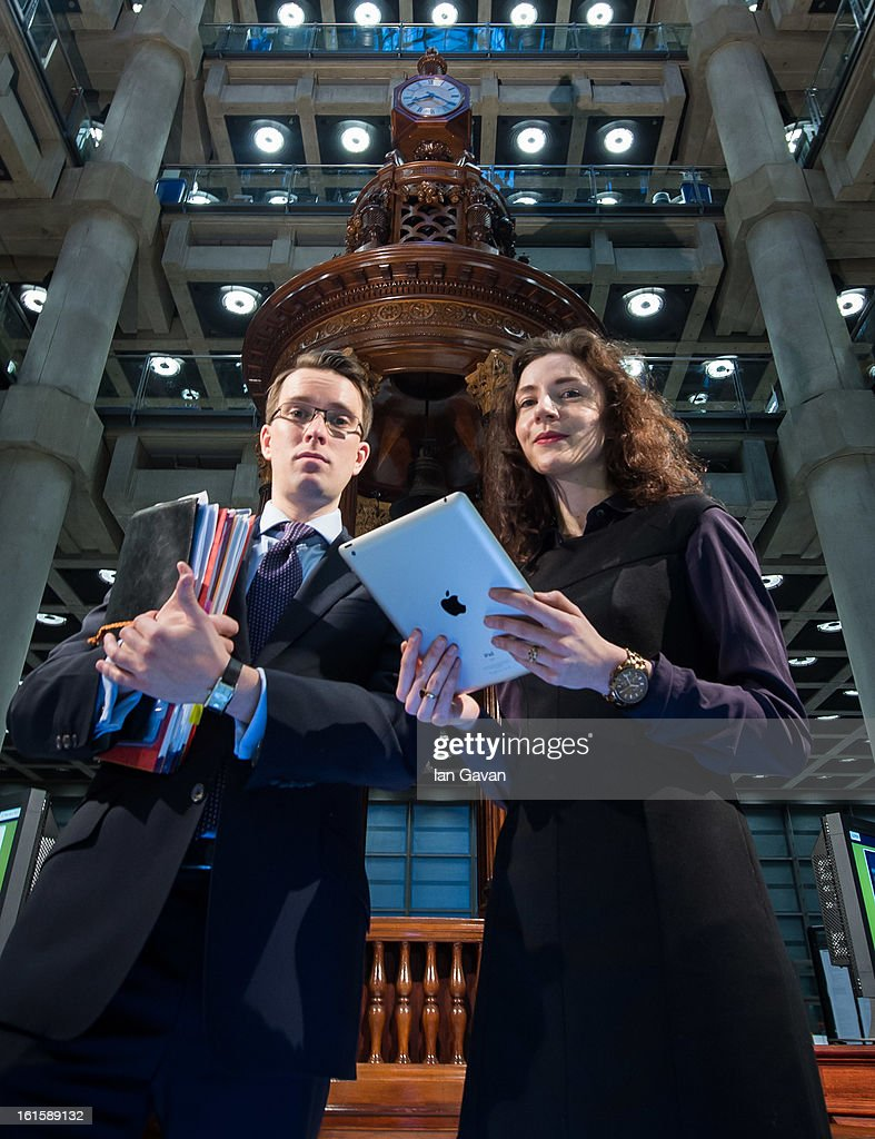 Alexandra Considine demonstrates the new iPad application to a colleague during the Xchanging Insurance iPad Application Launch at Lloyd's of London on February 12, 2013 in London, England. The application allows those in the market to abandon the traditional broker's slipcase and work on tablets for the first time in the centuries old insurance market.